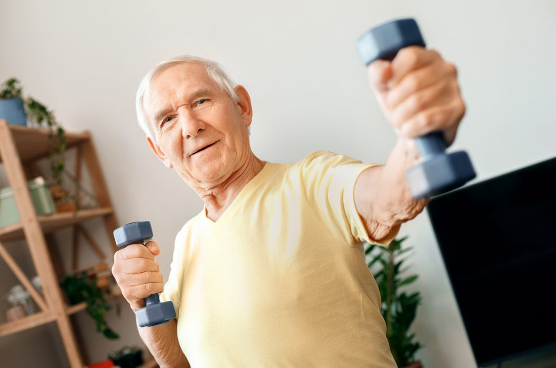 Elderly man lifting weights at home